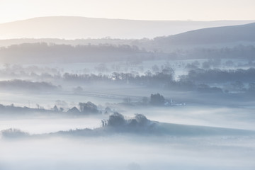 Stunning foggy English rural landscape at sunrise in Winter with layers rolling through the fields