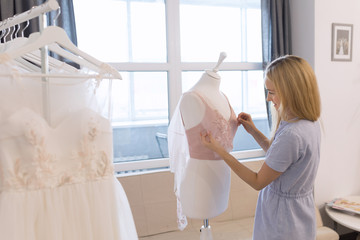 Front view of successful wedding dressmaker owner measuring materials on mannequin in office or workshop. Talented female seamstress working with textile for sewing clothes