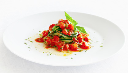 zucchini spaghetti with tomato sauce decorated with basil leafs
