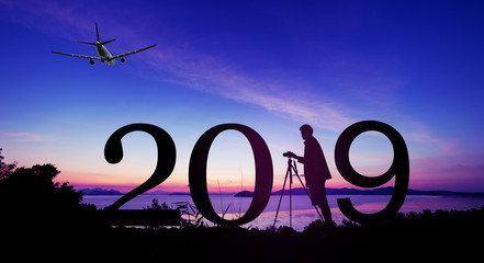Silhouette young photography man take a photo in sunrise or sunset beautiful scenery Enjoying on the hill and 2019 text,New year 2019 background concept.