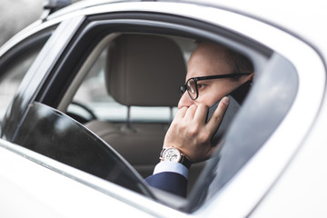 young successful businessman talking on the phone sitting in the back seat of an elite car, talks and business meetings