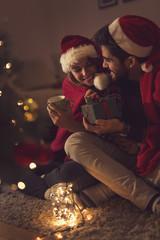 Couple sitting next to Christmas tree