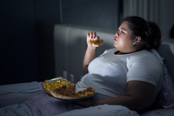 Fat woman eating pizza on bed