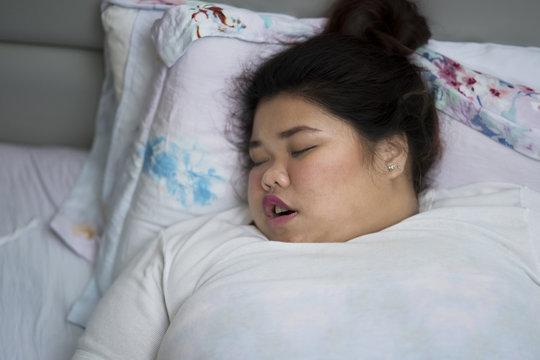 Overweight woman sleeping with open mouth, snoring