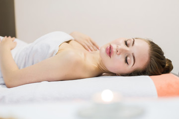 Young beautiful girl in spa salon. The girl lies on the couch for a massage after a rejuvenation procedure