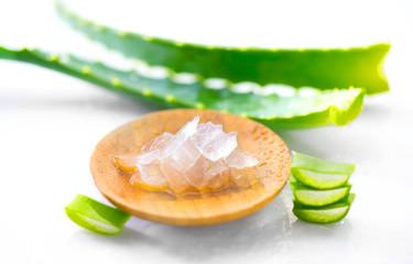 Fotoväggar - Aloe Vera leaves closeup on white wooden background. Organic sliced aloevera leaf and gel, natural organic cosmetic ingredients for sensitive skin, alternative medicine. Skincare concept