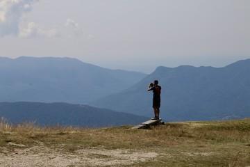 man taking picture mountain landscape