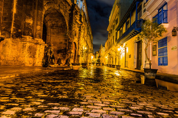 Night travel photography in Havana, Cuba. The colonial architecture of Havana. Limestone paved streets glowing in the night.