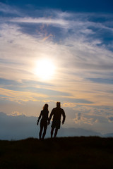 Couple in silhouette holding hands walking towards colorful clouds at sunset in the mountains