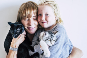 family portrait with  caucasian mother blonde beautiful middle age woman and young white skin son and two lovely adorable cats. group hug with persons and animals. best friends forever together