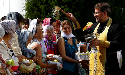 "Believers wait to be blessed by an Orthodox priest, at a church during the ""Yablochniy Spas"", or Apple the Saviour, a religious holiday in Minsk"