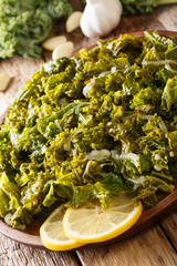 Vegetarian food: fried kale cabbage with onions and garlic close-up. vertical