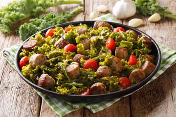 kale with grilled sausages, fresh tomatoes and garlic close-up on a table. horizontal