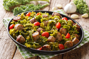 Delicious healthy food: organic kale cabbage with sausages, tomatoes and garlic close-up on a plate. horizontal
