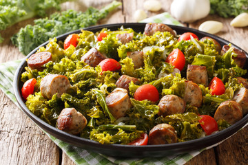 Stew kale leaf cabbage with sausages, tomatoes and garlic close-up on a plate on a table. horizontal