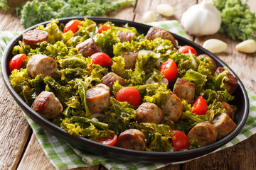 Spicy kale cabbage with fried sausages, tomatoes and garlic close-up on a plate. horizontal