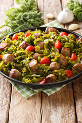 Warm salad of fried kale cabbage with sausages, tomatoes and garlic close-up on a plate. vertical