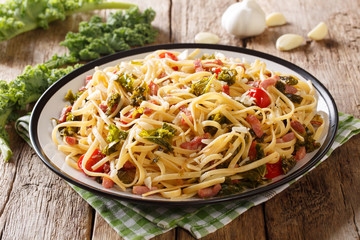 Organic food: pasta seasoned with fried bacon, parmesan cheese and vegetables close-up on the table. horizontal