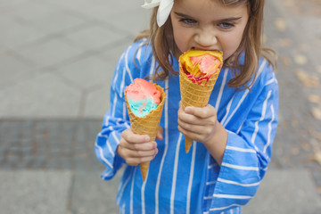 Little girl holding ice cream cone in her hands