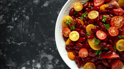 Healthy Red beans and mix of organic red and yellow cherry tomatoes salad topped with parsley.