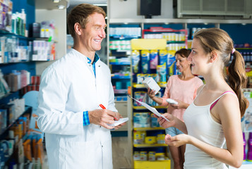 Laughing man pharmacist helping customers