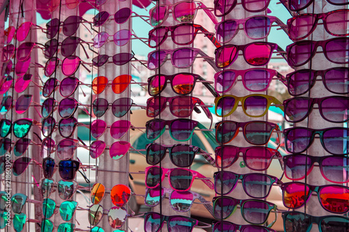 3a440ccdadb Pink glasses. Brilliant mirror pink sunglasses. A market tray with green  sunglasses. Many different green sunglasses. Sale of cheap glasses on the  street.