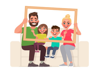Family portrait. Dad, mom, son and daughter sitting on the couch, holding a picture frame