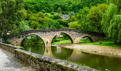 Belcastel medieval bridge with Aveyron river and green forest background , Aveyron, France