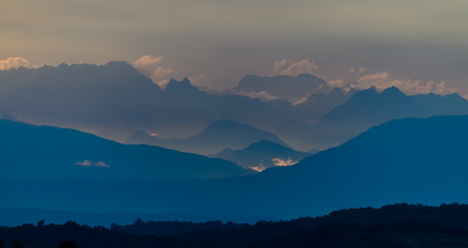 Dolomites in the morning with clouds above, sun rays illuminate the farthest mountain peaks