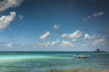 Beautiful beach view in Lombok Island with cloudy blue sky and traditional fishing boat