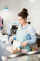 Waist up portrait of Hispanic young woman working in cafe, packing cakes in box to go standing behind counter