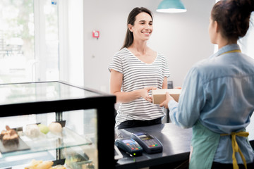 Waist up portrait of cheerful customer buying food in local shop and smiling happily, copy space