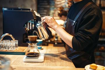 Fototapeta Male barista pours boiling water into the glass obraz