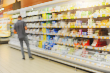 Blurred product shelves in the supermarket. Defocused background of store.