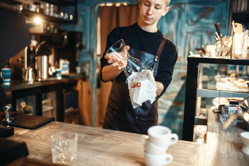 Male barista wipes the dishes after making coffee