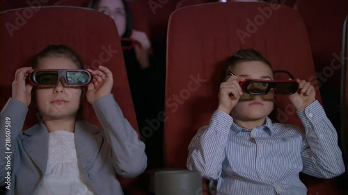 d6903c0a728 Children wearing 3d glasses at cinema chair. Brother and sister ...