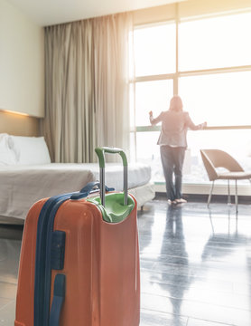 Traveller woman with luggage in business hotel guest room looking out toward city view staying for work travel or vacation trip