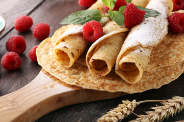 Homemade crepes served with fresh raspberrries and powdered sugar on rustic table.