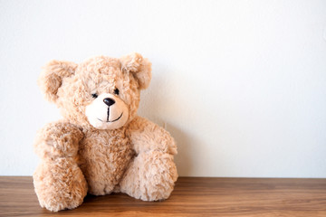 Cute Teddy Bear sitting alone with white wall on wooden table