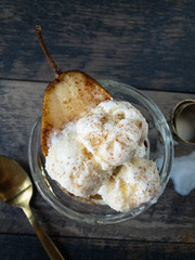 baked pear with vanilla icecream and cinnamon in glass flay lay