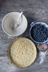 Ingrediants and pie crust for blueberry tart flat lay