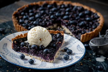 blueberry tart slice with vanilla icecream on plate