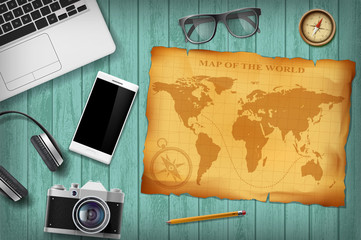 Green wooden table with technology devices and retro map. Travel background.
