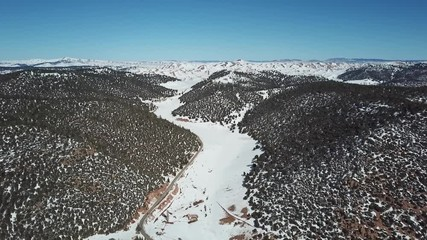Wall Mural - Aerial view of the road in snow-capped Atlas mountains covered with forest in Morocco at winter, 4k