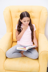 Enthusiastic about exciting story. Reading hobby. Girl child sit yellow armchair read book. Kid cute bookworm. Girl kid cute pajamas relax read fairytale book before sleep. Encourage useful habits