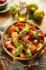 Tomato salad with addition fresh  basil, olive oil and spices. Vegan food with products from organic cultivation. Healthy eating concept