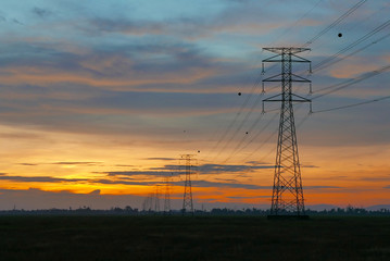 Sunset over electricity pylon on a paddy field at a village.
