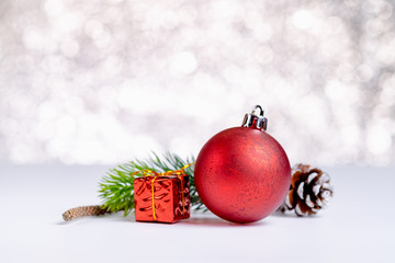 Close up group of red christmas glossy ball and gift box on white table at sparkling blue bokeh abstract blur background,Holiday seasonal greeting card,Leave space for adding text.