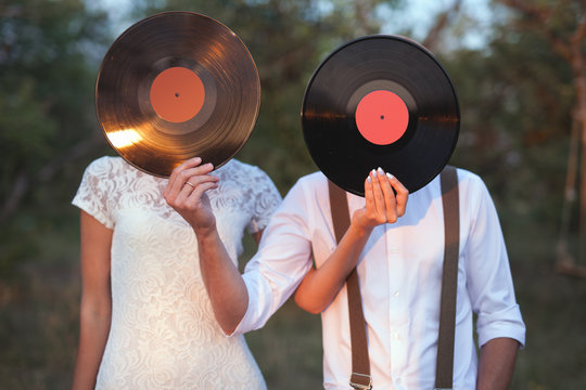 Conceptual Image of Man And Woman Hold A Vinyl Record Discs On Their Faces