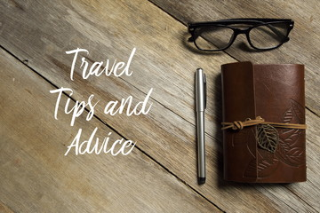 Top view of eyeglasses,pen and notebook on wooden background written with TRAVEL TIPS AND ADVICE.